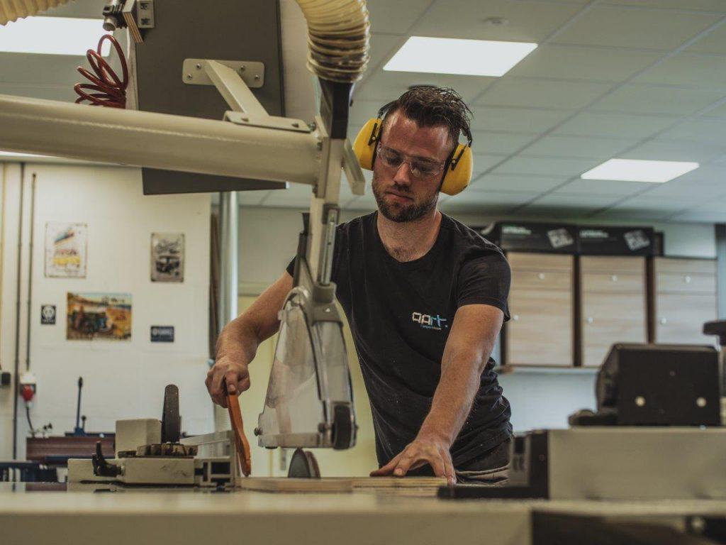 houtzagerij meubelmaker aan het werk met bril en gehoorbescherming